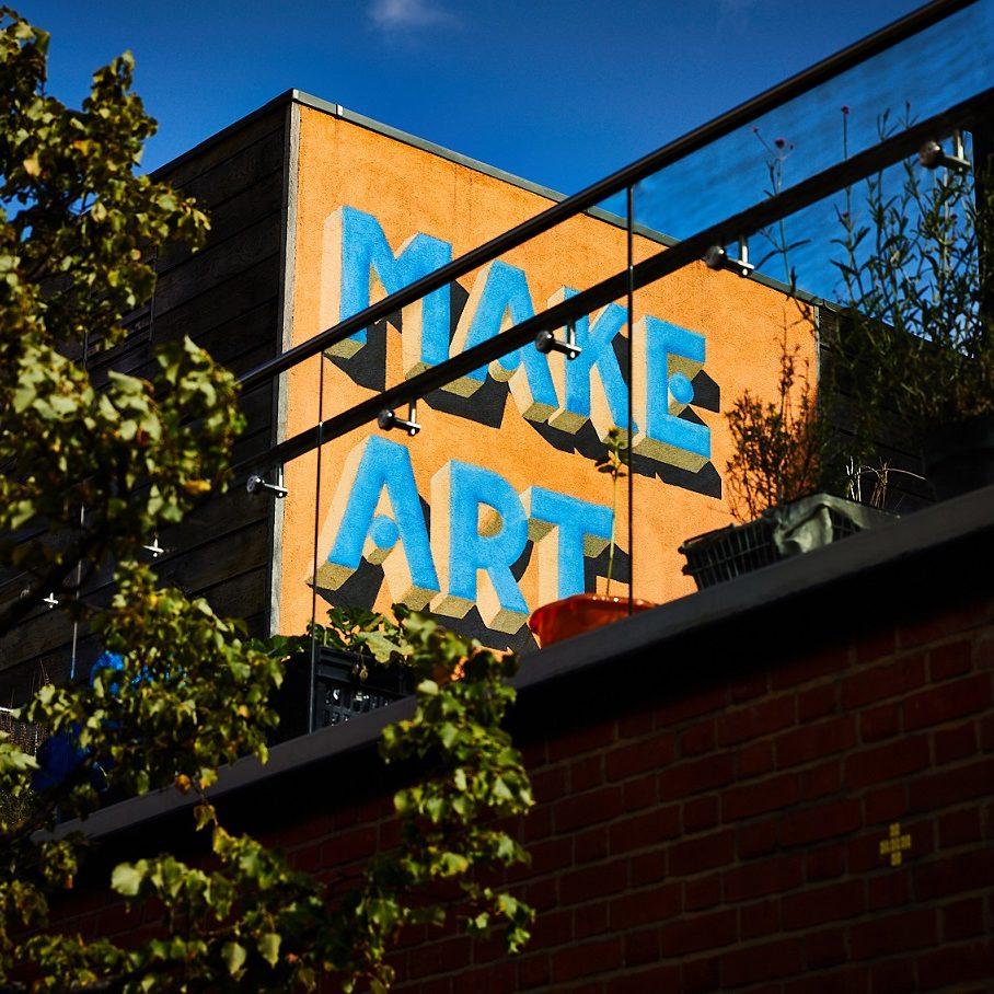 Detail of 'Make Art Now' mural on The Art House terrace taken from street level.