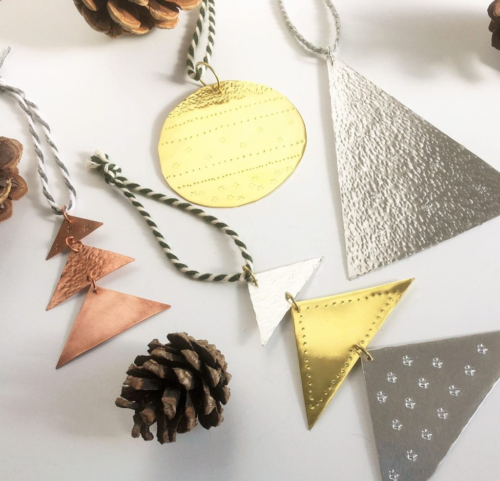 A range of metal Christmas Tree Decorations and pine cones placed on a white background