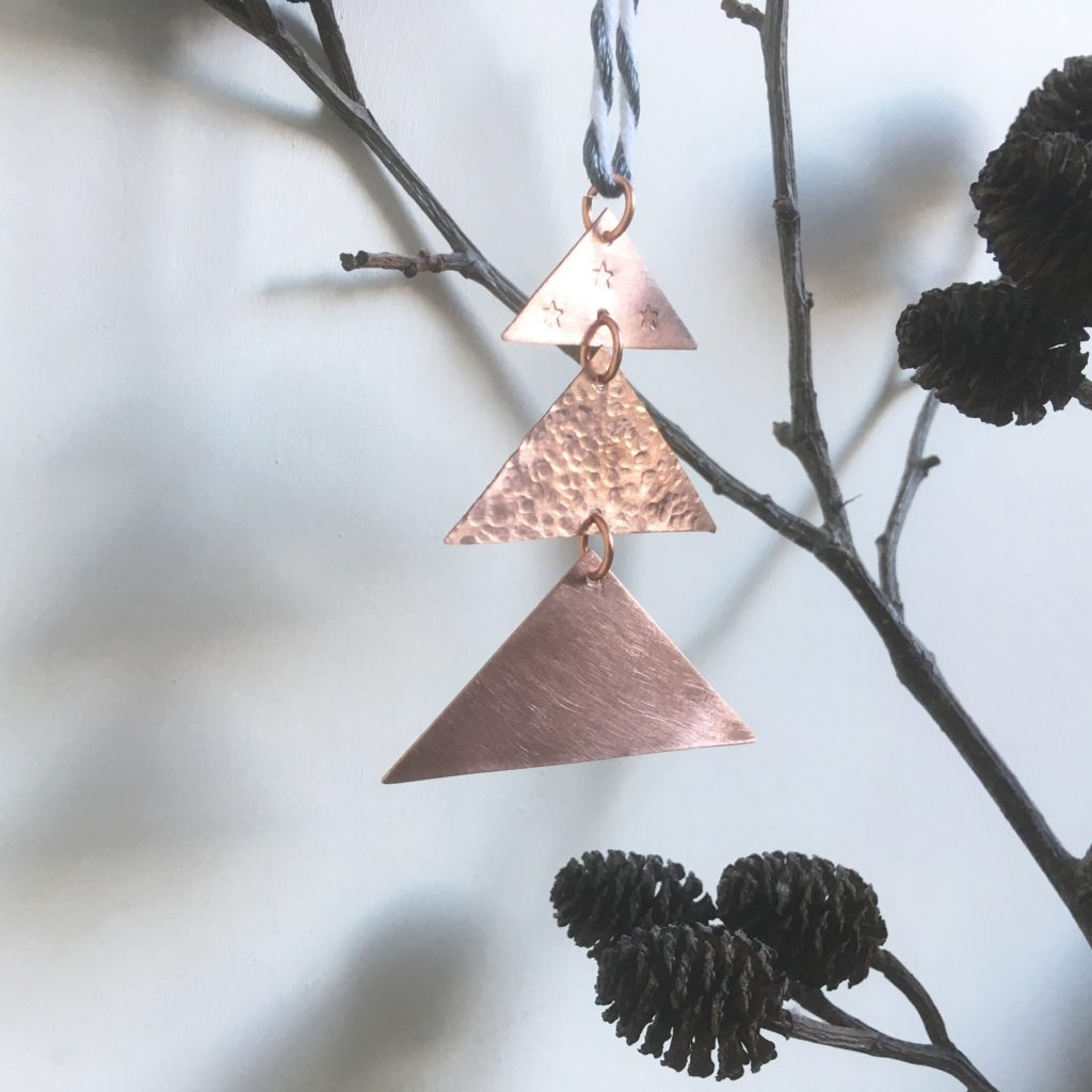 Metal Christmas Tree Decoration hung on a branch with pine cone, G.Broughton