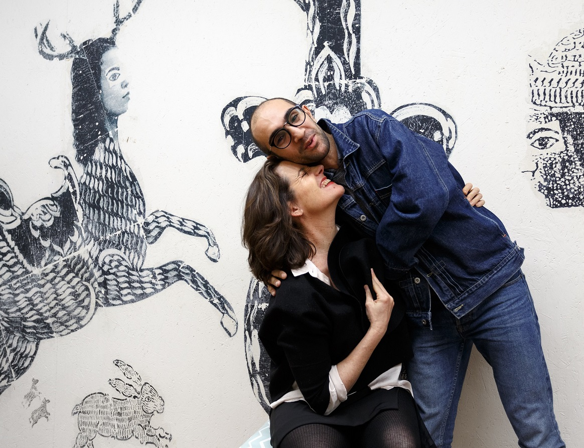 The Art House CEO Sydney Thornbury and SoS beneficiary Mo Barrangi in his studio, with large black and white mural on the wall behind them